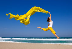 Jumping. Beautiful young woman jumping on  the beach with a colored tissue Royalty Free Stock Photo