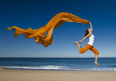 Jumping. Beautiful young woman jumping on the beach with a colored tissue Stock Image