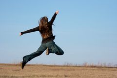 Jumping. Happy girl jumping around on dry field Stock Photo