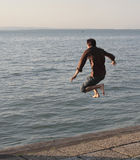 Jumping. Dressed man jumping into water Royalty Free Stock Photography