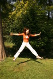 Jumping. A woman jumping in the air in a park, spreading her arms and legs Stock Image