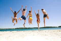 Jumping. Photo of young people�s backs jumping on the sea shore simultaneously stock photography