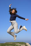 Jumping. Beautiful young woman jumping to the sky royalty free stock photography