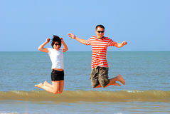 Jumping. Young Lovers Jumping in the beach Stock Photos