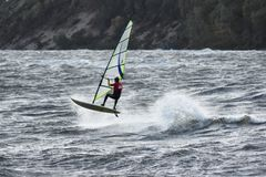 Jumping anonymous windsurfer in Baltic Sea stormy waters Stock Images