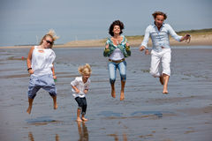 Jumping around. Happy young family at the beach jumping Stock Image
