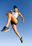 Jumping athlete. Athlete jumping shot from low angle with sky background Royalty Free Stock Images