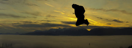 Jumping backpacker on sunset Royalty Free Stock Images