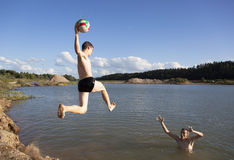 Jumping With a Ball. The boy throwing a ball while jumping into the pond Stock Photography