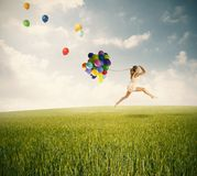 Jumping with balloons Royalty Free Stock Photo