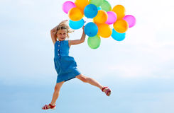 Jumping with balloons Royalty Free Stock Image