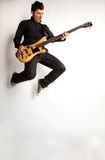 Jumping bass player on a white background Stock Photos