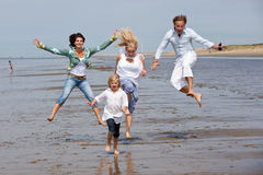 Jumping on the beach. Happy young family at the beach jumping Stock Image