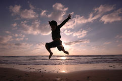 Jumping on the beach stock photography