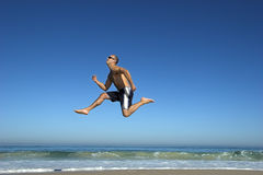 Jumping on the beach. Man making a big jump on the beach royalty free stock photo