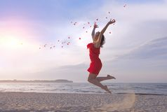 Jumping beautiful woman in red dress throwing rose petals on beach. royalty free stock photography