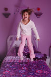 Jumping on the bed. A cute young girl jumping on her bed Stock Photos