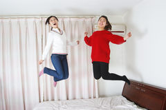 Jumping on the bed of Chinese women Royalty Free Stock Image
