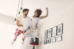 Jumping on bed. Happy loving couple having fun while jumping on bed Stock Image