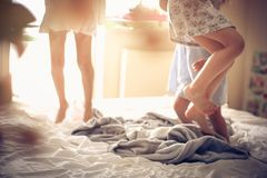 Jumping on bed. Three little girls jumping on bed. Close up. Space for copy royalty free stock photo
