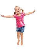 Jumping blonde child. Adorable little girl jumps in studio, having fun, isolated on white stock photos