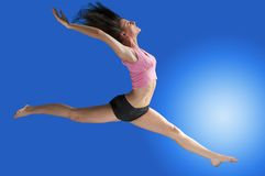 Jumping in blue. A cute gymnast in a hard jump on a blue background Stock Photography