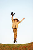 Jumping boy. Jumping child explorer with binoculars and safari hat playing adventure games outdoors stock photos