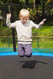 Jumping boy. Blond boy jumping on trampolin at an outdoor playground Stock Photos