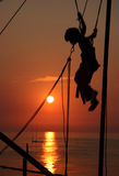 Jumping Boy. Boy jumping on an elastic rope of a trampoline. Beautiful ocean sunset scene in background. Slovenia Stock Photos