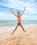 Jumping boy on the beach. With sea on background Royalty Free Stock Photo