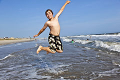 Jumping boy enjoys the beautiful ocean Stock Photo