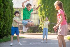 Jumping boy and friends with skipping rope