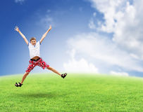 Jumping boy on the grass. Sky. Royalty Free Stock Photography