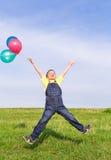 Jumping boy on green field Stock Photo