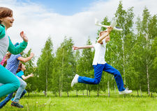 Jumping boy with white airplane toy and children Royalty Free Stock Images