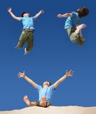 Jumping boys, sitting boy with hands up on beach Royalty Free Stock Image