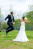 Jumping bridegroom and his bride Royalty Free Stock Photography