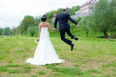 Jumping bridegroom and his bride Royalty Free Stock Images