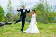 Jumping bridegroom and his bride Stock Photography