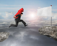 Jumping businessman carrying arrow up sign to flag on cliff Royalty Free Stock Image