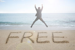 Jumping businessman cheering with free word handwritten in sand Royalty Free Stock Images