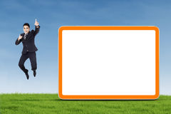 Jumping businessman on green field Stock Photography