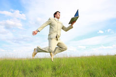 Jumping businessman with laptop Royalty Free Stock Photos