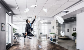 Jumping businessman in office . Mixed media. Funny jumping businessman in modern 3D rendering interior. Mixed media Royalty Free Stock Photos