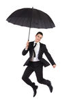 Jumping businessman with an umbrella Royalty Free Stock Photos