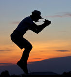 Jumping cameraman's silhouette. Royalty Free Stock Image