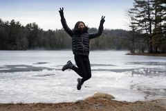 Jumping Chinese woman on beach winter. A chinese woman jumping and flashing peace signs on the beach at Burr Pond State Park in wintertime in Torrington royalty free stock photos