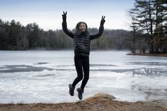 Jumping Chinese woman on beach winter. A chinese woman jumping and flashing peace signs on the beach at Burr Pond State Park in wintertime in Torrington royalty free stock photography