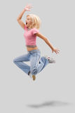Jumping with clipping path. Dancing woman with blond hair and happy smiling facial expression jumping up. Studio isolated on white background with clipping path Royalty Free Stock Image