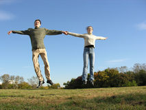 Jumping couple. Meadow stock image